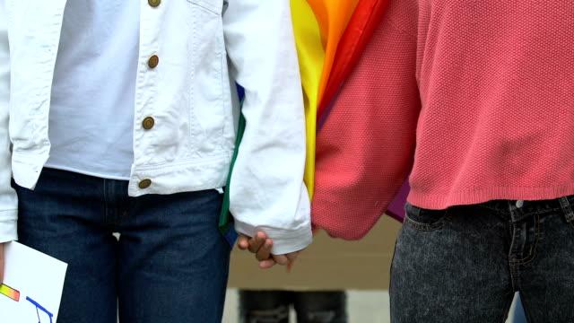 Weibliches-Paar-nimmt-Hände-halten-LGBT-Rechte-Plakat-Unterstützung-für-Homo-Ehe