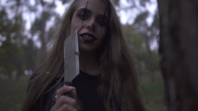 Crazy-young-woman-with-Halloween-clown-makeup-on-her-face-holding-big-knife-in-hand-laughing-