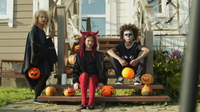 Three-Kids-in-Halloween-Costumes-Sitting-on-Porch