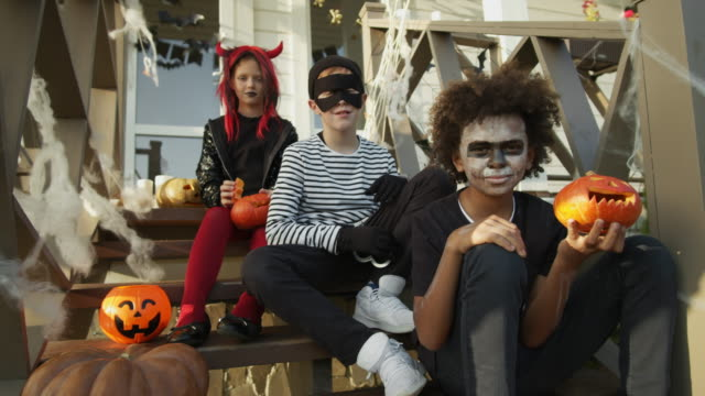 Three-Teenagers-Wearing-Halloween-Costumes-Sitting-on-Porch
