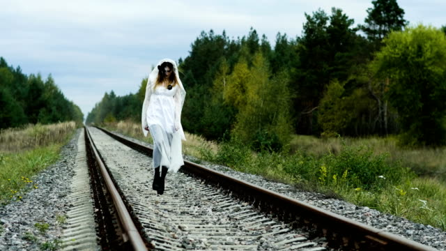 A-woman-with-make-up-of-dead-bride-for-Halloween-in-wedding-gown-on-the-rails-4K