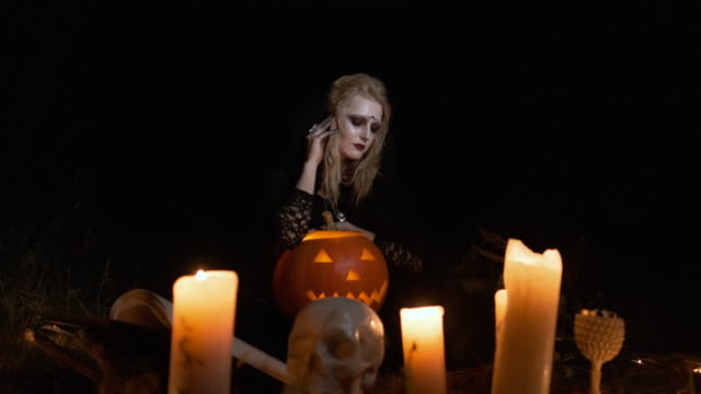 Halloween-Image-Young-Witch-In-Black-Clothes-Holds-Pumpkin-In-Her-Hands-