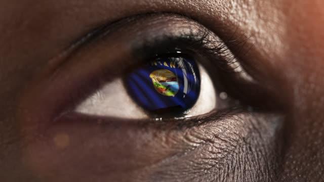 Frau-schwarzes-Auge-in-Nahaufnahme-mit-der-Flagge-von-Montana-Staat-in-Iris,-vereinigte-Staaten-von-Amerika-mit-Windbewegung.-Videokonzept