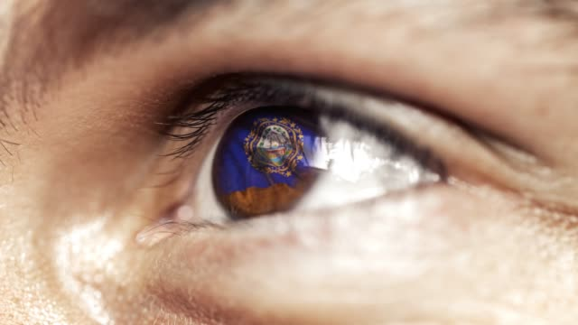 Man-with-brown-eye-in-close-up-the-flag-of-New-Hampshire-state-in-iris-united-states-of-america-with-wind-motion-video-concept