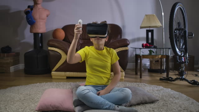 Young-Caucasian-teen-with-curly-hair-in-VR-headset-holding-remote-control-and-looking-around-Child-using-virtual-reality-Augmented-reality-VR-glasses-generation-Z-Cinema-4k-ProRes-HQ-