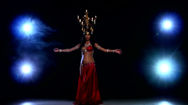 Attractive-belly-dancer-woman-dancing-with-candles-on-her-head-black-smoke
