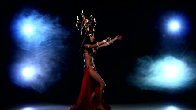 Attractive-belly-dancer-girl-dancing-with-candles-on-her-head-black-smoke