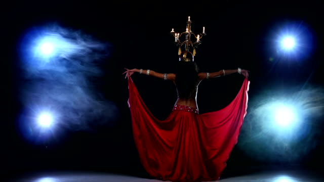 Attractive-belly-dancer-girl-continue-dancing-with-candles-on-her-head-black-smoke