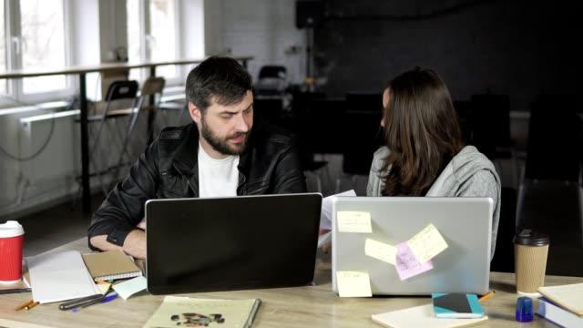 Jóvenes-oficinistas-discutiendo-frente-a-sus-computadoras-portátiles-Mujer-mostrando-papeles-muy-enojado-Slowmotion