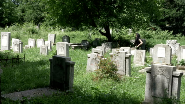 Young-woman-dressed-in-funeral-clothes-walking-in-cemetery-among-the-graves