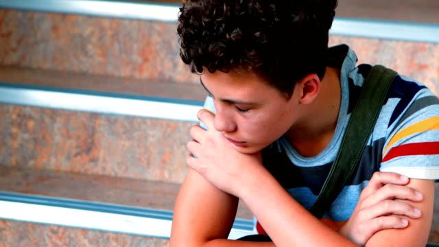 Sad-schoolboy-sitting-alone-on-staircase