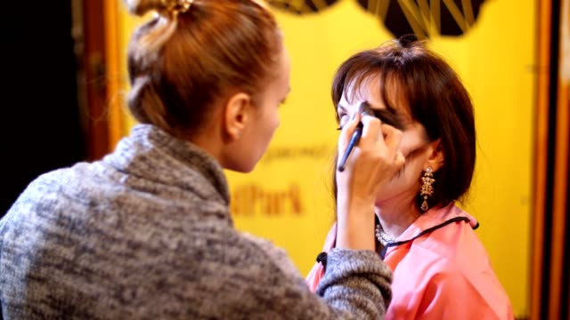 Halloween-Party-Make-up-Artist-zieht-eine-schreckliche-Make-up-auf-dem-Gesicht-eine-Brünette-Frau-für-eine-Halloween-Party-im-Hintergrund-sieht-man-die-Landschaft-im-Stil-von-Halloween