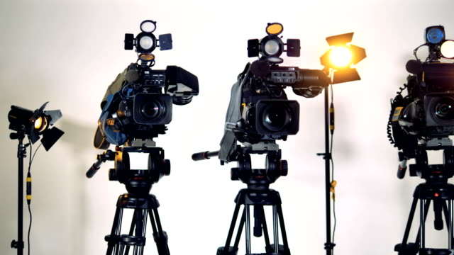 Three-professional-video-cameras-on-tripods-