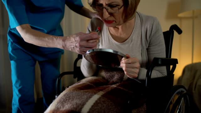 Mental-disorder-woman-applying-lipstick-and-nurse-taking-makeup-away-lost-time