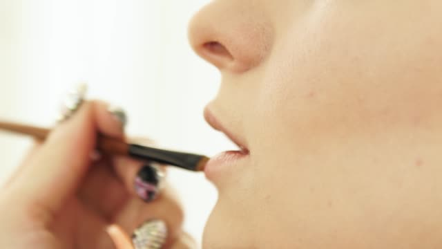 Mujer-Maquillaje-artista-aplicar-labial-en-modelo-de-maquillaje-de-labios-con-cosméticos-cepillo-cerca