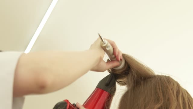 Hairdresser-hairstyling-long-hair-with-brush-and-dryer-after-hairdressing-Close-up-haircutter-drying-long-hair-with-dryer-and-hairbrush-Finish-hairdressing-in-beauty-salon