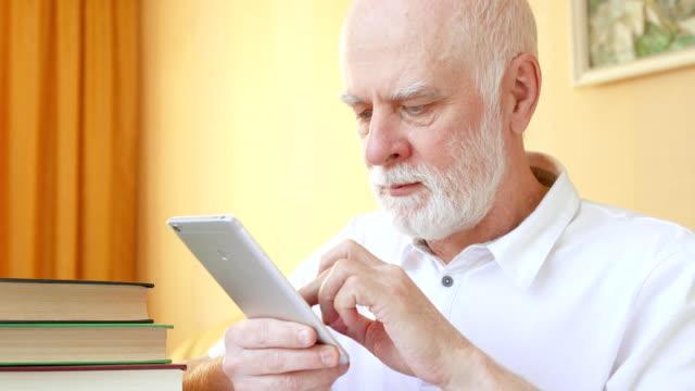 Senior-hombre-con-aplicación-para-el-aprendizaje-de-lenguas-extranjeras-en-smartphone-haciendo-la-formación-en-la-aplicación