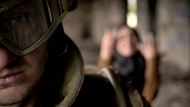 Soldado-armado-mirando-a-cámara-cuando-la-mujer-musulmana-en-hijab-gritando-y-llorando-detrás-de-hombre-abandonado-edificio-de-fondo-concepto-terrorista