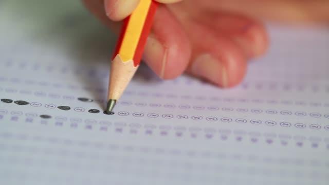 Prueba-de-examen-con-lápiz-el-dibujo-seleccionados-cuestionarios-de-opción-múltiples-o-pruebas-de-exámenes-de-estudiantes-de-educación-contestar-ejercicios-de-hojas-en-la-escuela-el-aula-universitaria-de-la-Universidad