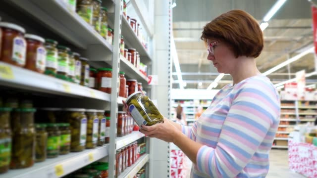 Caucasian-woman-standing-near-shop-shelves-and-choosing-pickles-in-grocery-market
