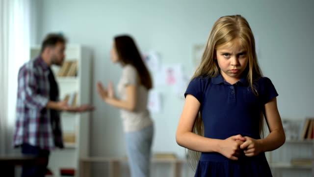 Frightened-girl-nervously-twisting-fingers-scared-by-parents-quarrel-violence