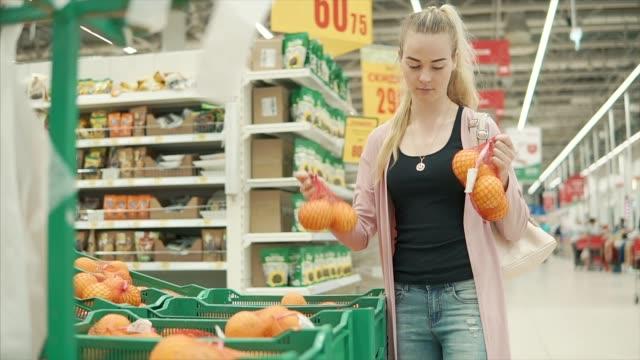 Joven-rubia-tiene-paquetes-con-naranjas-en-un-supermercado
