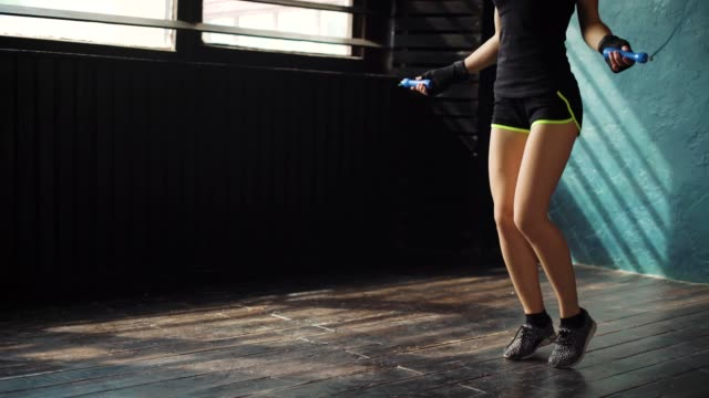 Junge-zielgerichtete-ernsthafte-Boxerin-in-umschlossenen-Bandage-Faust-Hände-springen-auf-Springseil-im-Fitness-Studio