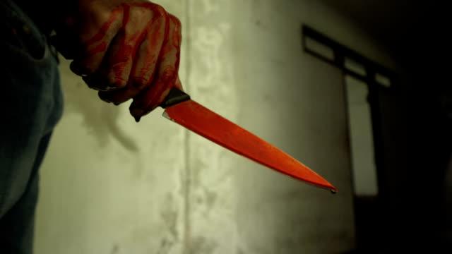 Closeup-foto-de-mano-sosteniendo-un-cuchillo-sangriento-con-sangre-goteando