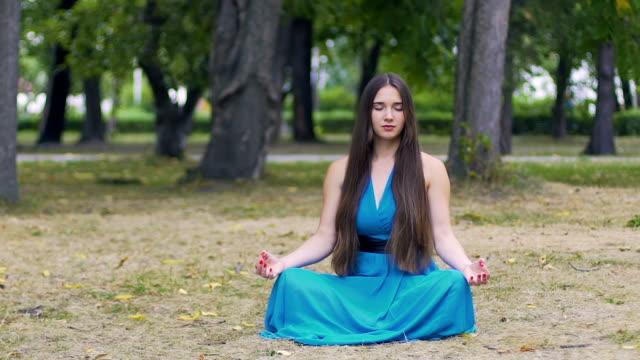 Schöne-Frau-im-blauen-Kleid-in-Lotus-stellen-meditieren-im-Park-langsame-Dolly-Pfanne