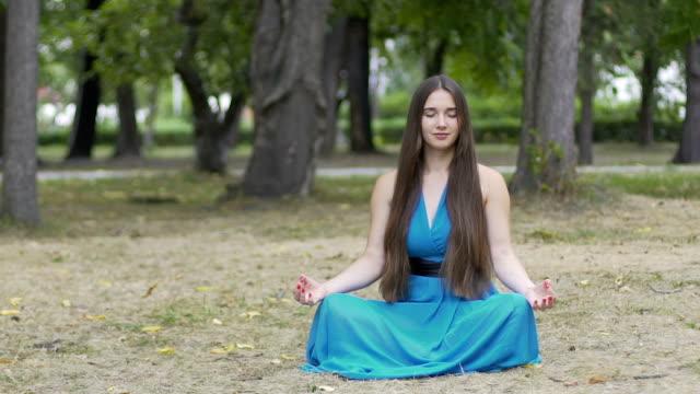 Schöne-Frau-im-blauen-Kleid-meditiert-im-Freien-für-Anzeigentext-Dolly-Schuss