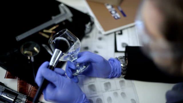 Detective-in-gloves-lifting-fingerprints-on-wine-glass-using-brush-and-powder