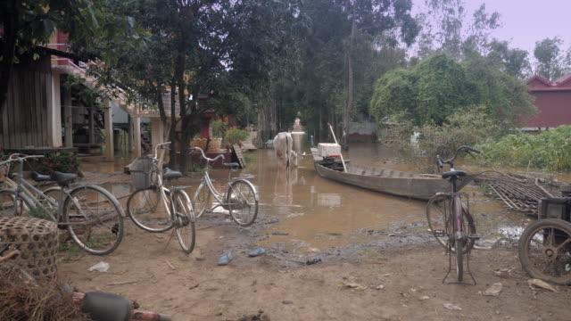 Bauer-führt-eine-Kuh-zum-Feld-durch-ein-überfluteten-Dorf-während-der-Monsunzeit