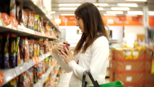 Young-woman-standing-in-a-ketchup-bottle-in-the-hands-of-a-supermarket-Happy-buyer-makes-purchases-in-the-supermarket-