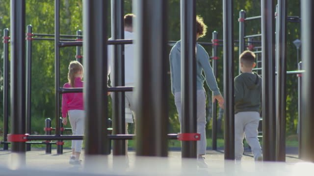 Sporty-Parents-Walking-with-Kids-on-Outdoor-Workout-Playground