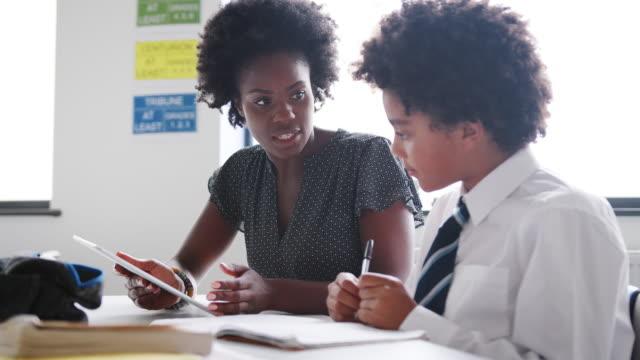 Weibliche-High-School-Lehrer-mit-Digital-Tablette-geben-männlichen-Studenten-tragen-einheitliche-Einzelunterricht-am-Schreibtisch