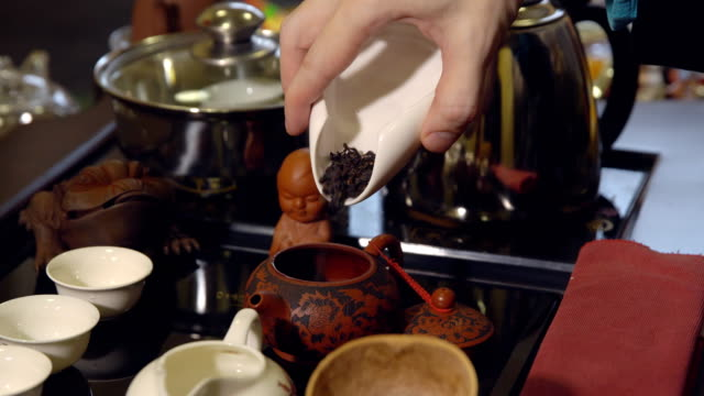 Tea-ceremony-Master-pours-tea-leaves-in-a-teapot