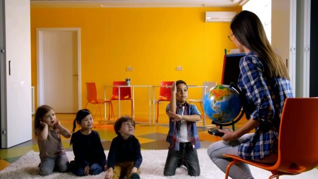 Preescolar-niños-estudiando-el-mundo-junto-con-el-profesor