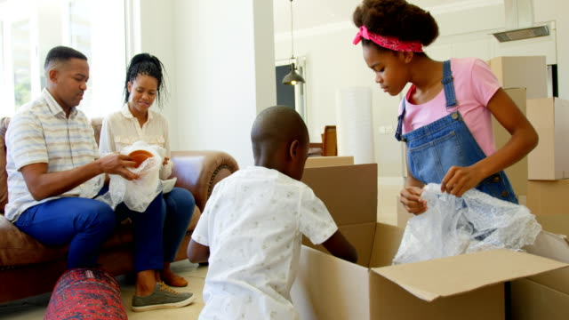 Front-view-of-young-black-family-unpacking-cardboard-boxes-in-a-comfortable-home-4k
