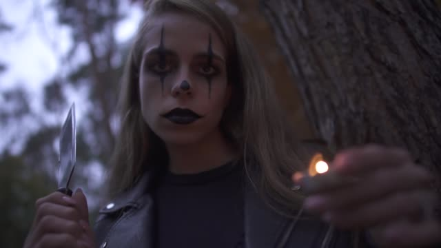 Pretty-blonde-psycho-girl-with-horrifying-Halloween-make-up-holding-hatchet-and-small-candle-in-hands