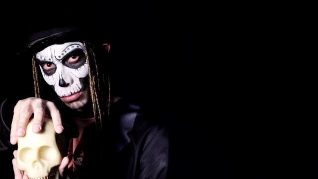 Retrato-del-hombre-en-traje-de-brujo-para-Halloween-acariciando-cráneo-en-sus-manos