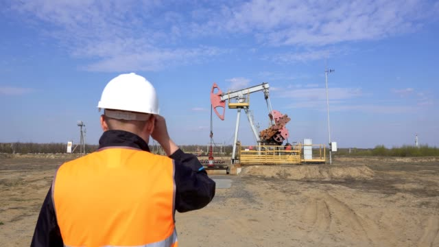 A-young-working-engineer-in-a-signal-vest-straightens-a-protective-helmet-on-his-head-against-the-background-of-an-oil-and-gas-rocking-machine-an-industry-copy-space-pumpjack