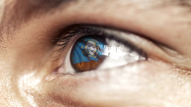 Man-with-brown-eye-in-close-up-the-flag-of-South-Dakota-state-in-iris-united-states-of-america-with-wind-motion-video-concept