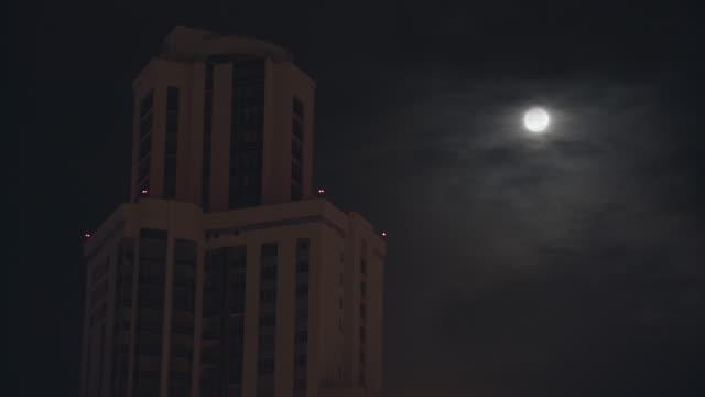 Paisaje-urbano-nocturno-con-un-edificio-alto-sobre-el-fondo-del-cielo-oscuro-Material-de-archivo-Luna-llena-en-cielo-oscuro-nublado