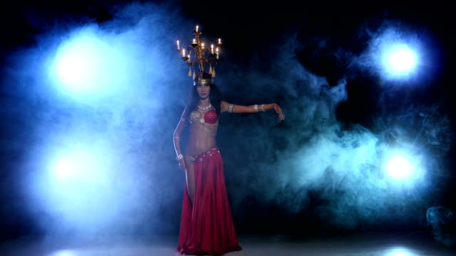 Attractive-belly-dancer-dancing-with-candles-on-her-head-black-smoke
