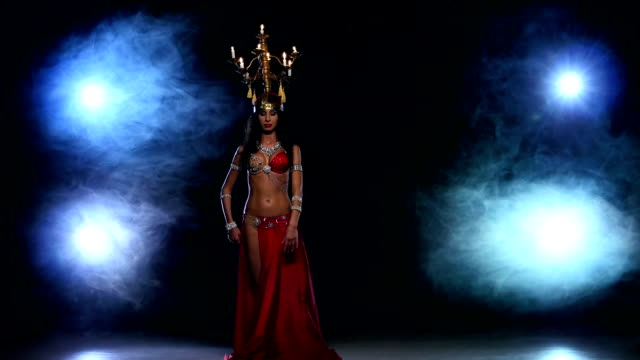 Attractive-belly-dancer-go-on-dancing-with-candles-her-head-black-smoke