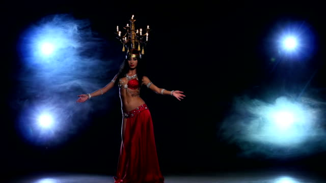 Attractive-belly-dancer-girl-starts-dancing-with-candles-on-her-head-black-smoke