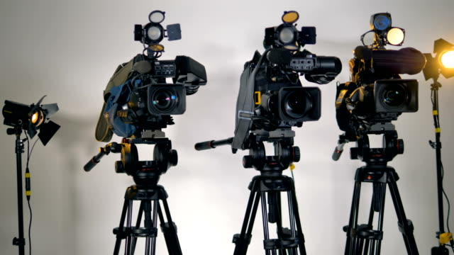 A-row-of-several-professional-cameras-on-tripods-