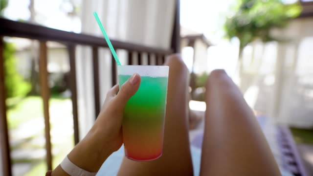 slim-tanned-womans-legs-and-hand-is-holding-glass-with-cocktail-with-straw-woman-is-lying-on-a-deck-chair-in-a-sunny-garden-in-daytime
