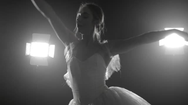 Professional-ballerina-dancing-ballet-in-spotlights-on-big-stage-Beautiful-caucasian-young-girl-wearing-white-tutu-dress-Black-and-white-vintage-retro-effect-tonned-4k