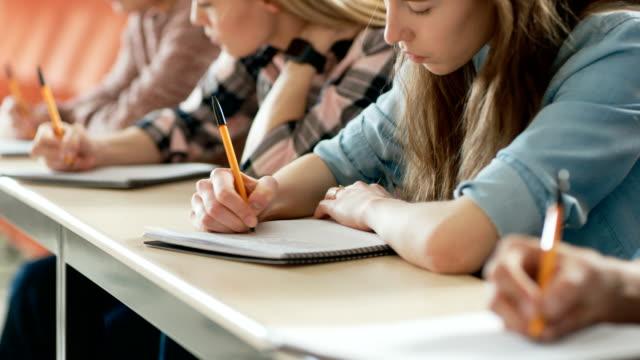 Filmfootage-aus-einer-Reihe-von-Multi-ethnischen-Schüler-im-Klassenzimmer-Prüfung-/-Test-Holding-Stifte-und-Schreiben-in-Notebooks-im-Fokus-Helle-Jugendliche-Studie-an-der-Universität-